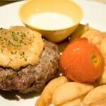 Hamburguesa con queso de cabra, cebolla, patatas gajo y tomate horneado