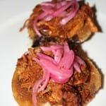 Panuchos con frijol negro, carne de cerdo marinado y cebolla morada picante sobre una base de pasta de maiz