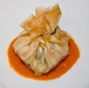 Plato caser: Paquetito de brick con juliana de verduras y pollo, con salsa de tomate y pimiento rojo