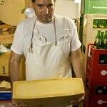 El quesero Guido Gimünder se las vió y se las deseó para voltear a mano el queso de 60kg.