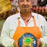 El encargado de Inma, uno de los puestos del mercado, posa junto con un queso Leonés