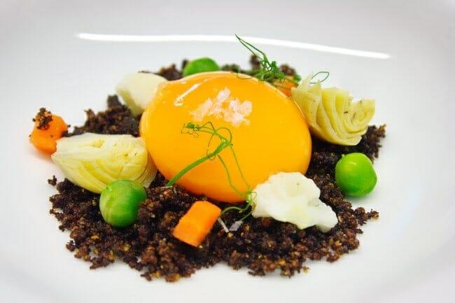 Tierra de morcilla con verduras y, yema de huevo trufado, antes de completarse con la crema de parmesano