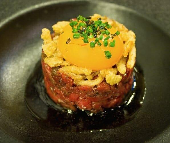 Steak tartar con sopa de soja y asados y su yema de huevos de corral