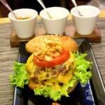 Hamburguesa 100% carne de buey con pan exclusivo, queso cheddar curado, tomate verde y cebolla frita, y acompañada con gajos de patatas fritas al pimentón de la vera
