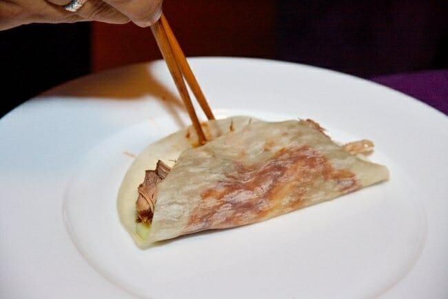 Detalle del crepe con pato crispy, cebolleta y pepino, ya casi listo para tomar