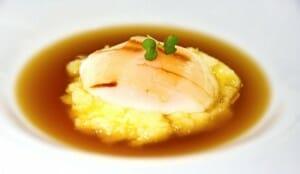Huevo de caserío asado con caldo de garbanzos, patata rota y láminas de tocino ibérico