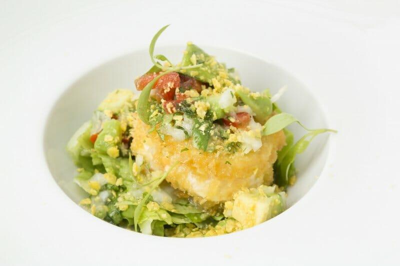Ensalada de hojas verdes con queso de cabra, guacamole y nachos