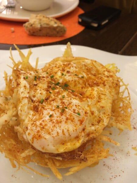 Huevos fritos sobre nido de patatas pajas