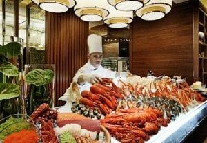Cocinero junto a un buffet de mariscos