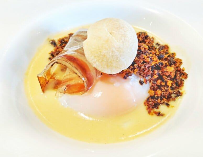 Cremoso de queso ahumado, huevo escalfado y migas de ajo negro